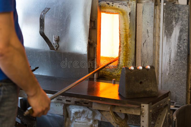 Manufacture worker heats glass in oven for heating the glass. Manufacture worker heats glass in stove for heating the glass. close up shot, focus on open stove stock image