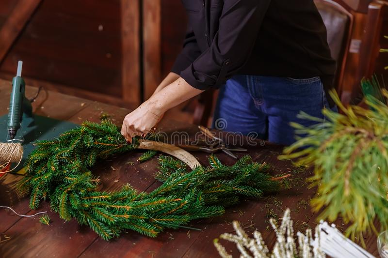 Young Cute smiling Woman designer preparing Christmas Evergreen Tree Wreath. Manufacturer of Christmas decor with their royalty free stock images
