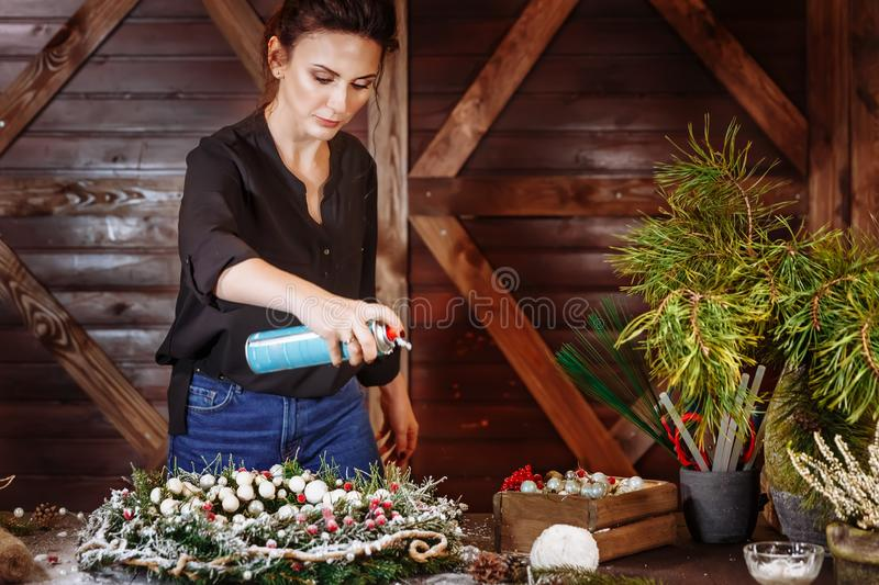 Young Cute smiling Woman designer preparing Christmas Evergreen Tree Wreath with artificial snow. Manufacturer of royalty free stock photography
