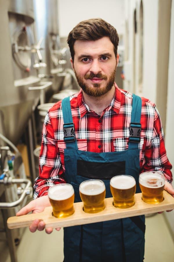 Manufacturer holding beer samples at distillery. Portrait of manufacturer holding beer samples at distillery royalty free stock image