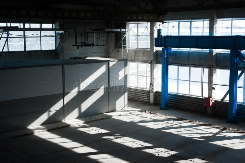 Manufacturing factory. Empty hangar building. Blue toned background. The production room with large windows and metal structures stock photo