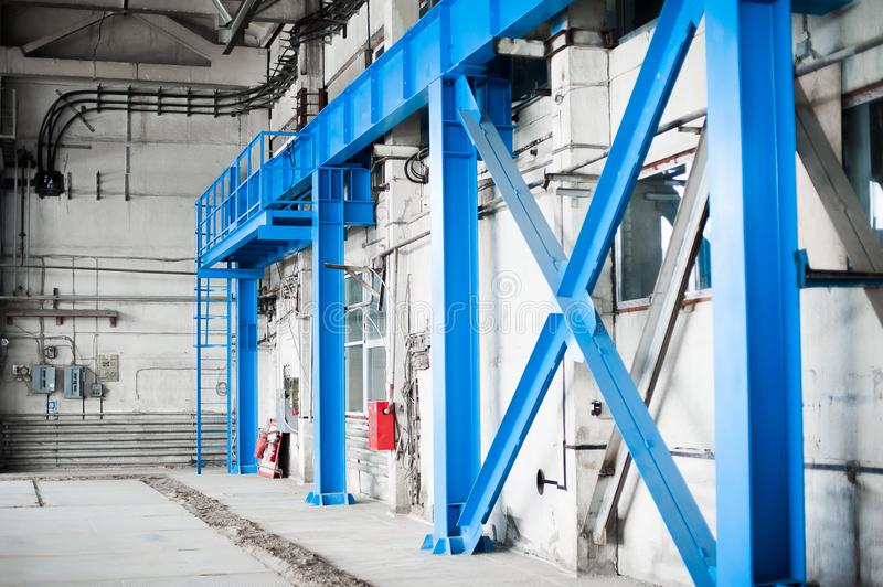 Manufacturing factory. Empty hangar building. Blue toned background. The production room with large windows and metal structures. Russian manufacturing factory royalty free stock image