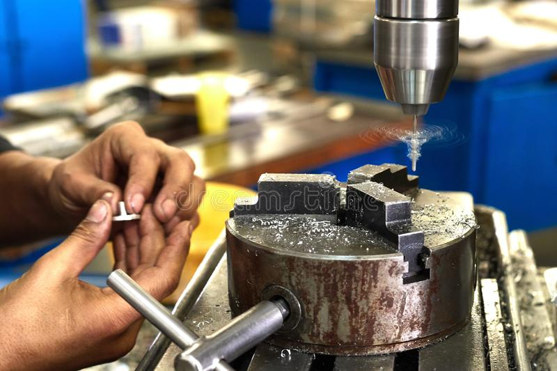 The manufacturing process of a small metal part on a drilling machine. Production factory line. Hole in the detail. Drill. Hands of a specialist royalty free stock image