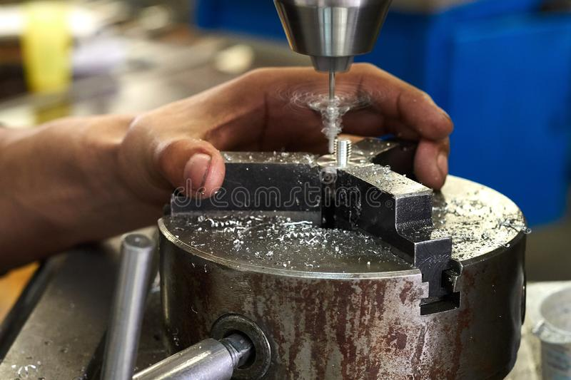 The manufacturing process of a small metal part on a drilling machine. Production factory line. Hole in the detail. Drill. Hands of a specialist royalty free stock photo