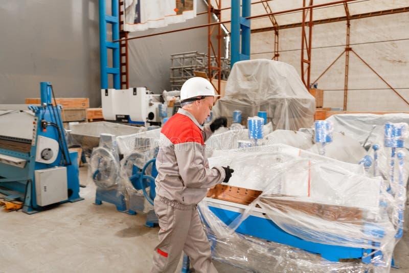 Manufaktura warsztat Pracownik odpakowywa maszynę w magazynie produkcja wentylacja i rynny Narzędzie i zdjęcie royalty free