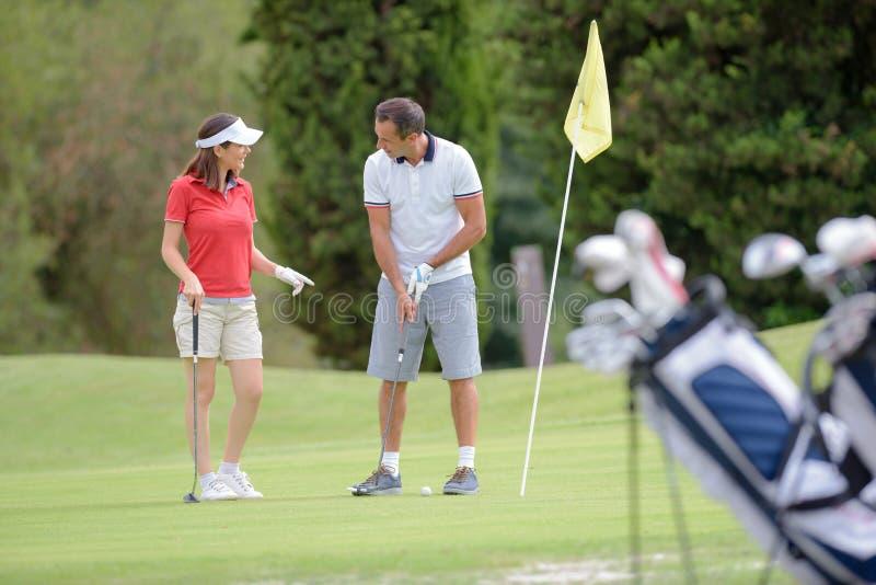 Manundervisningkvinna hur man spelar golf royaltyfri fotografi