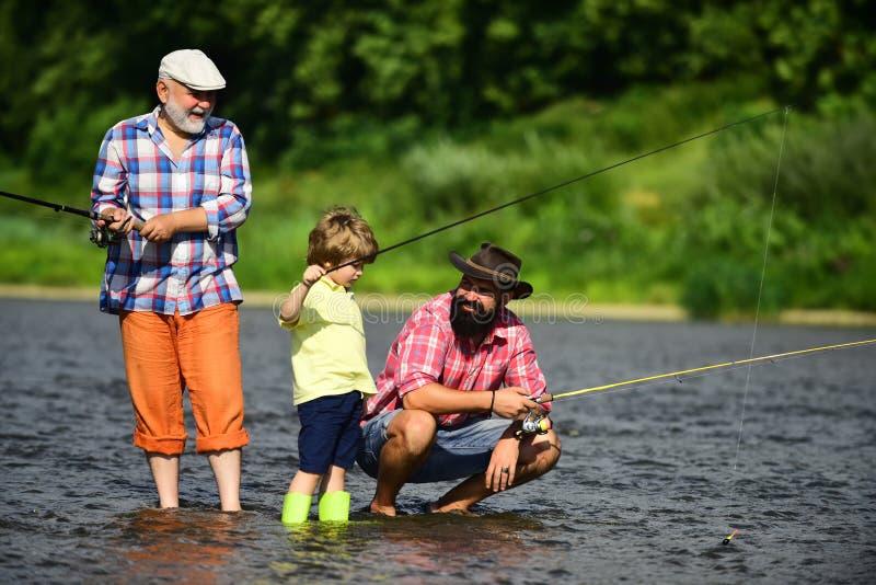 Manundervisningungar hur man fiskar i floden Fader-, son- och farfarfiske Alla ?ldras kategorier - sp?dbarns?lderen, barndom, ton arkivfoto