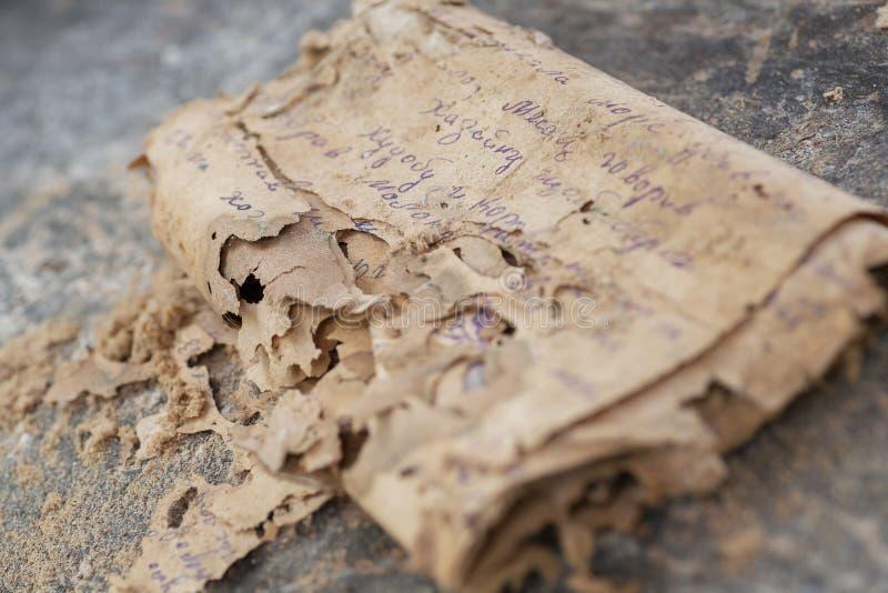 Manuscrito del papel histórico en una lengua desconocida antigua, estropeada por el tiempo y los insectos Concepto secreto del te fotos de archivo