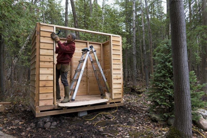 Manusje van alles die Cedar Storage Shed bouwen royalty-vrije stock foto