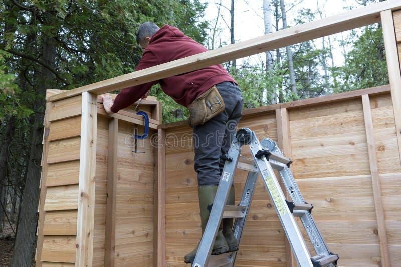 Manusje van alles die Cedar Storage Shed bouwen stock fotografie