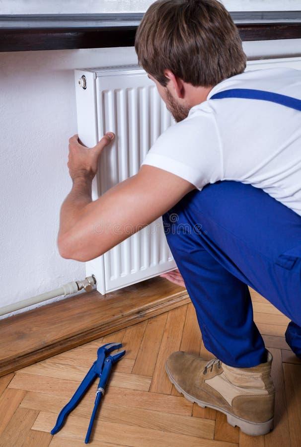 Manusje van alles die een radiator installeren stock foto