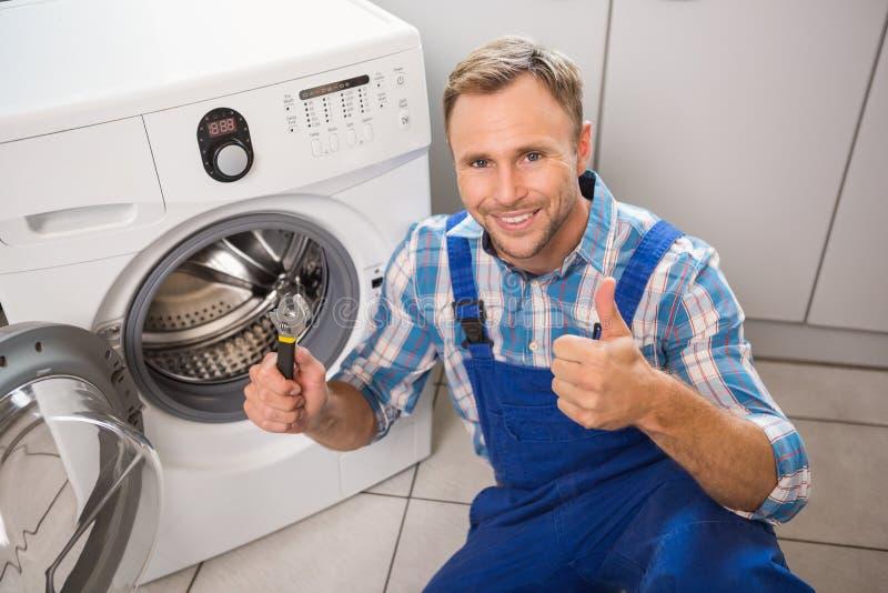 Manusje van alles die een wasmachine bevestigen stock afbeelding