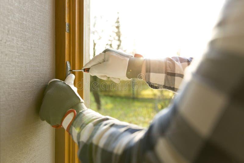 Manusje van alles die het venster met schroevedraaier bevestigen stock foto
