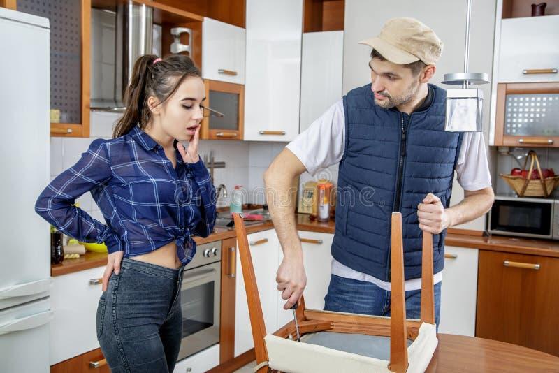 Manusje van alles die meubilair in de keuken herstellen Hij herstelt een stoel met een schroevedraaier royalty-vrije stock afbeeldingen