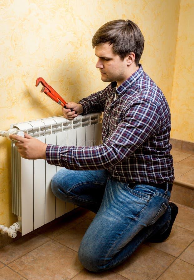 Manusje van alles het bevestigen het verwarmen radiator met rode loodgieterbuigtang stock fotografie