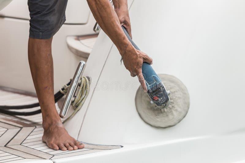 Manutenção do iate Um lado de lustro do homem do barco branco no imagens de stock royalty free