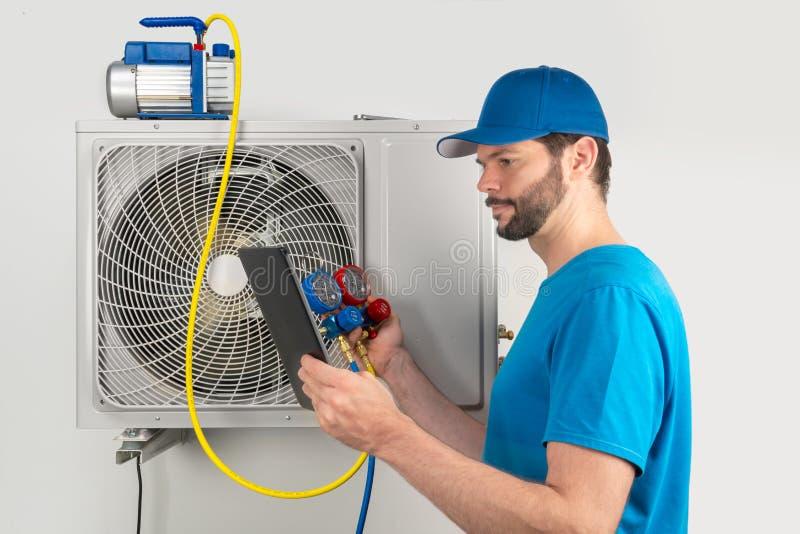 A manutenção do reparo do reparo do serviço da instalação de uma unidade exterior do condicionador de ar, pelo trabalhador techni imagens de stock
