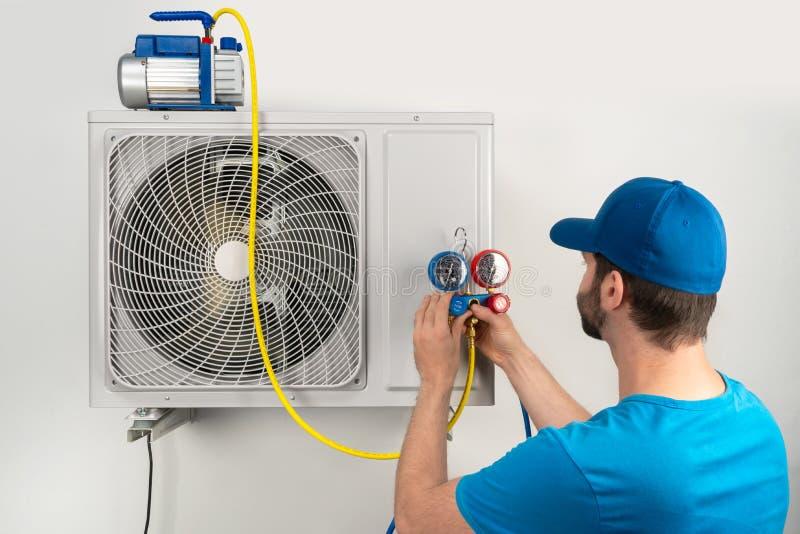 A manutenção do reparo do reparo do serviço da instalação de uma unidade exterior do condicionador de ar, pelo trabalhador techni imagens de stock royalty free
