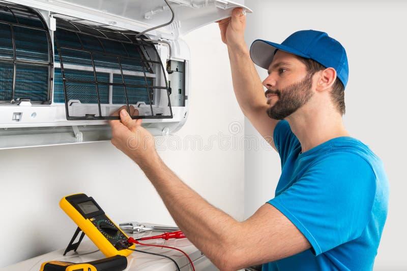 Manutenção do reparo do reparo do serviço da instalação de uma unidade interna do condicionador de ar, pelo trabalhador technican imagem de stock royalty free