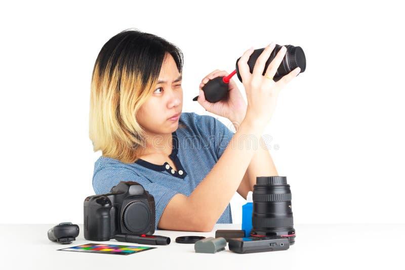 Manutenzione della donna una macchina fotografica di DSLR con il brower della polvere in sua mano immagine stock libera da diritti