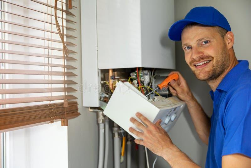 Manutenzione sorridente e tecnico di assistenza di riparazione che lavora con la caldaia del riscaldamento a gas della casa fotografie stock