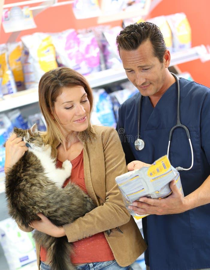 Manveterinär som råder klienten med katten arkivfoton