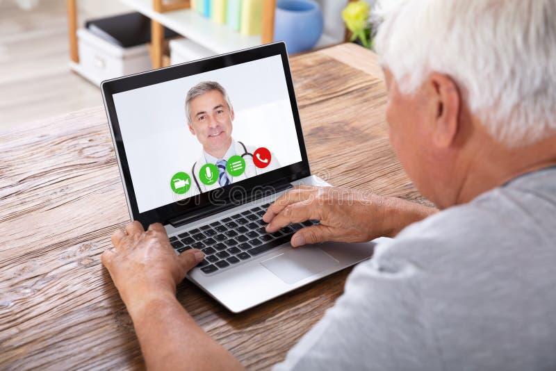 ManvideoConferencing med doktor On Laptop royaltyfri foto