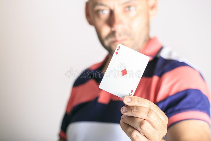 Manvisning som spelar kortet i hans hand arkivfoton