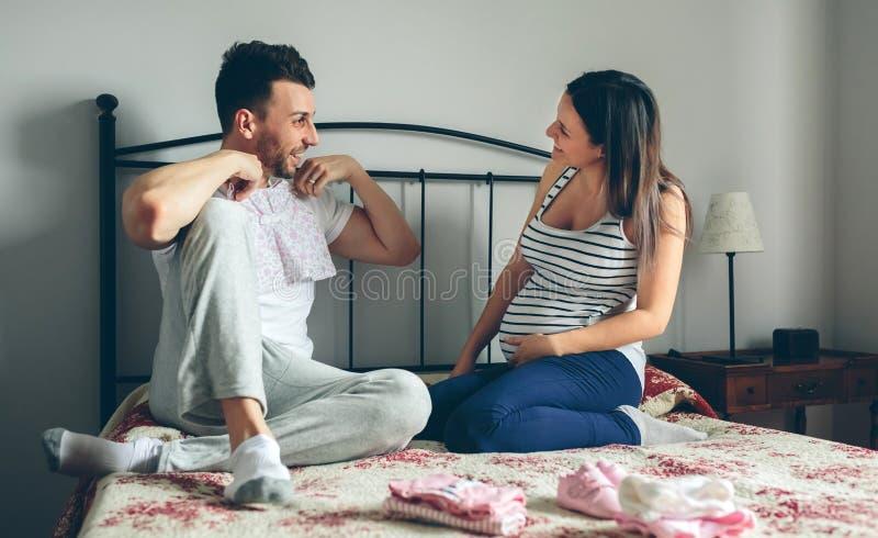Manvisningen behandla som ett barn kläder till gravida kvinnan arkivfoto