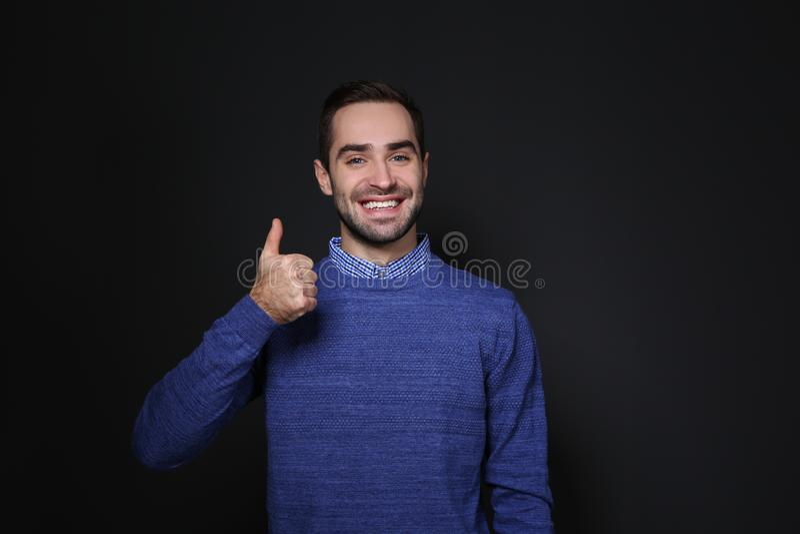 ManvisningTUMME UPP gest i teckenspråk på svart arkivbild