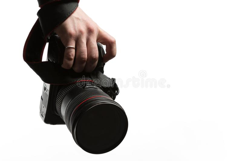 A manwith a ring on his finger  holding in the hand a DSLR camera close-up. Isolated on white background. A man with a ring on his finger  holding in the hand a stock photo