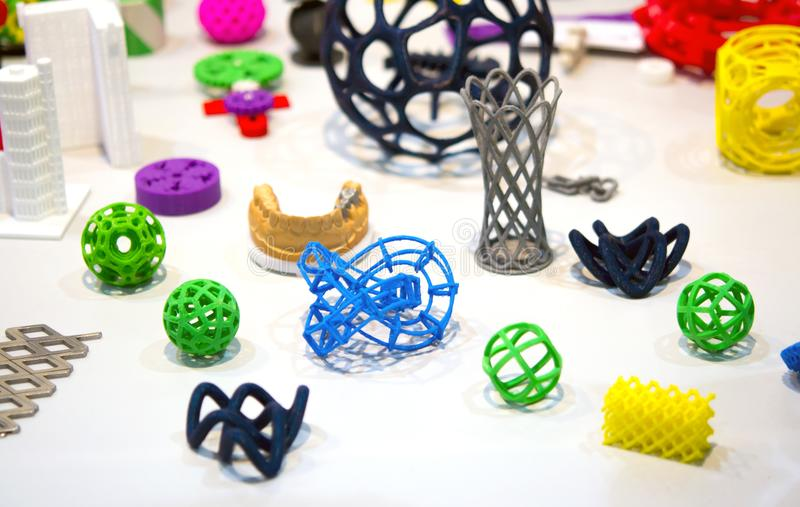 Many abstract models printed by 3d printer close-up. Many abstract models bright colorful objects printed on a 3d printer on a white table. Fused deposition stock photography