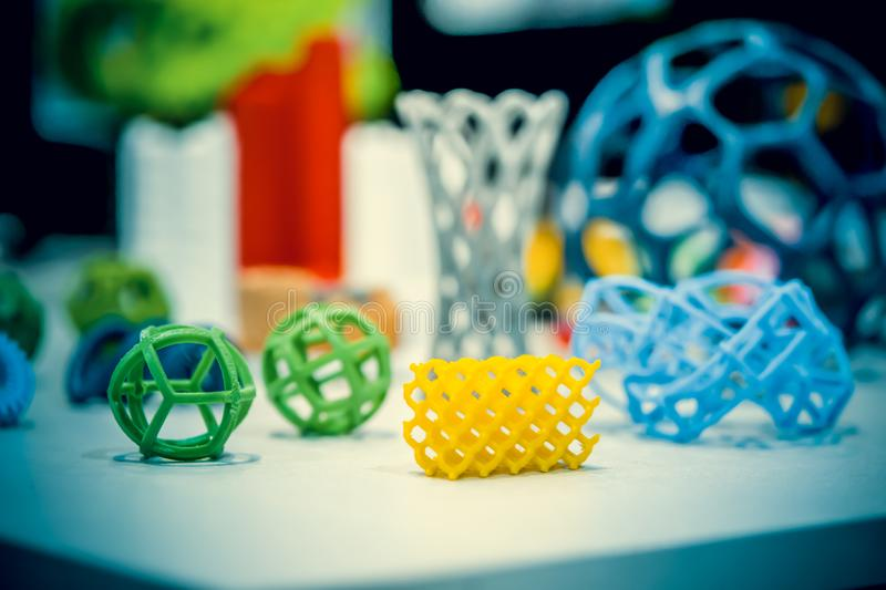 Many abstract models printed by 3d printer close-up. Many abstract models bright colorful objects printed on a 3d printer on a white table. Fused deposition royalty free stock images