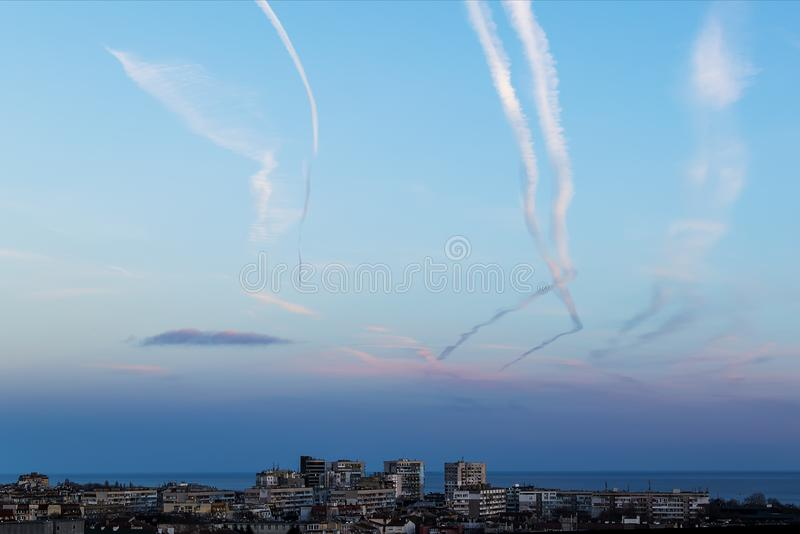 Many airplane contrails in a clear sky over the city. Jets of airplane in the blue sky stock photo