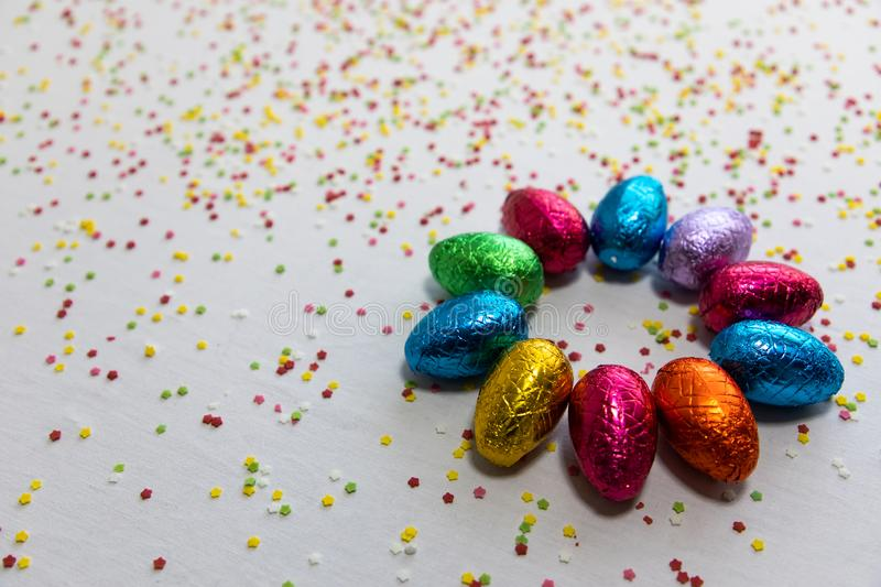 Many aligned colored chocolate easter eggs on white background and colorful confetti stock photo