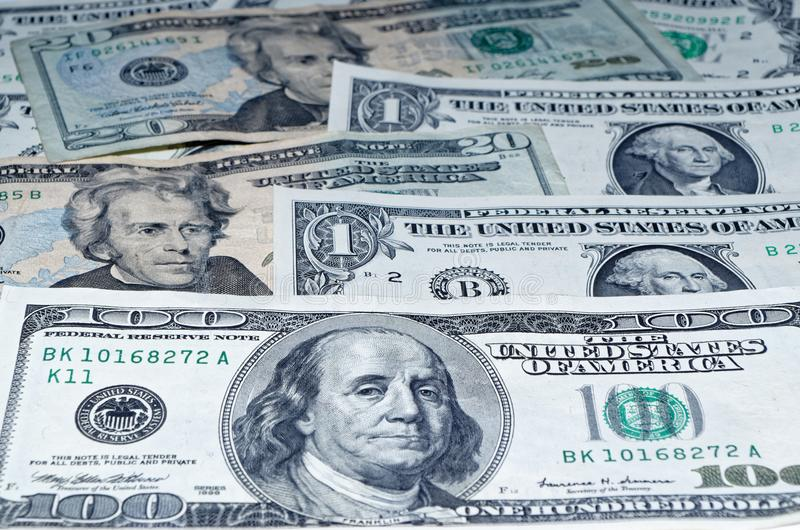 Many american dollars as laid out as a background. Many american dollars laid out as a background with focus on one hundred dollars banknote in foreground royalty free stock photography