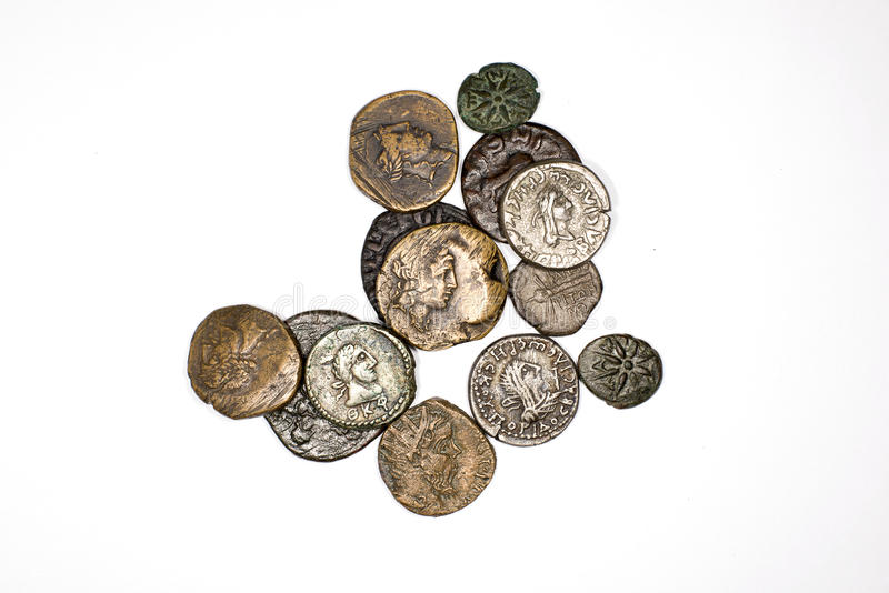 Many ancient bronze and silver coins on a white background. Many ancient bronze and silver coins with portraits on a white background stock photos