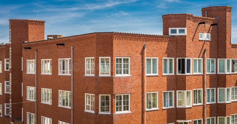 Typical old red brick housing building with hooks in Amsterdam, North Holland, the Netherlands. Many apartments and flats in a typical housing structure in the royalty free stock images