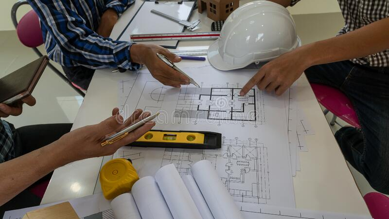 Many architects and engineers are meeting the construction planning with many tools. On the table stock photos