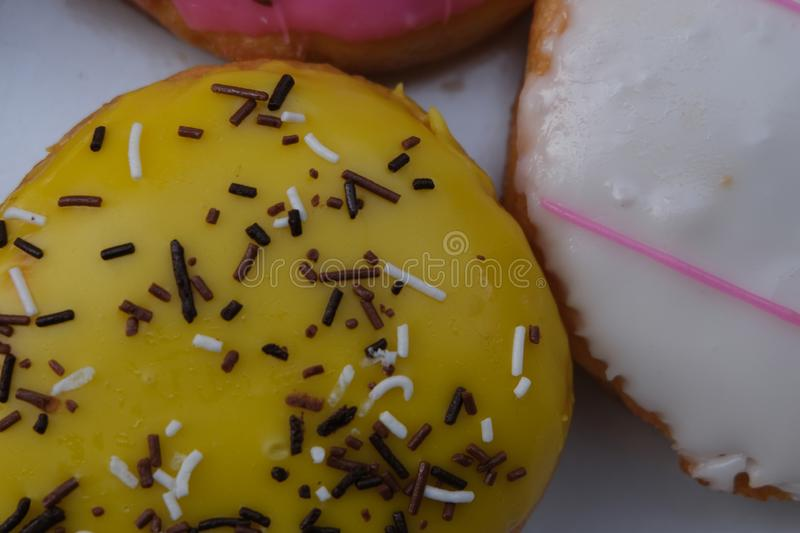Fresh donuts with colorful glaze in the box. Many Assorted donuts on a background royalty free stock photo