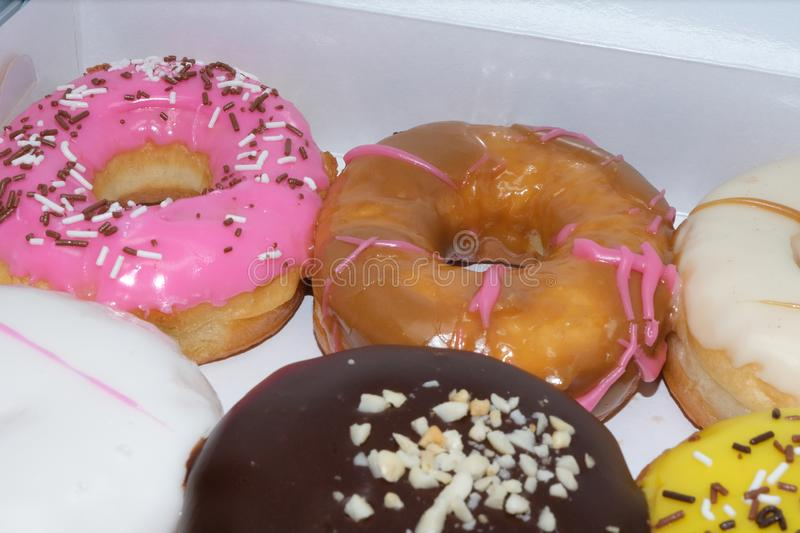 Fresh donuts with colorful glaze in the box. Many Assorted donuts on a background stock photography