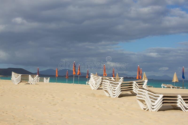 Many beach umbrella and chair on horizon line. Closed beach parasol on sky background. Tropic bay. Perfect seaside. Many beach umbrella and chair on horizon stock photos