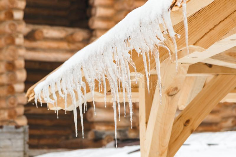 Many icicles melt on the wooden roof with water drops. Spring is comming. Many beautiful icicles melt on the wooden roof at the end of winter and water drops stock photos