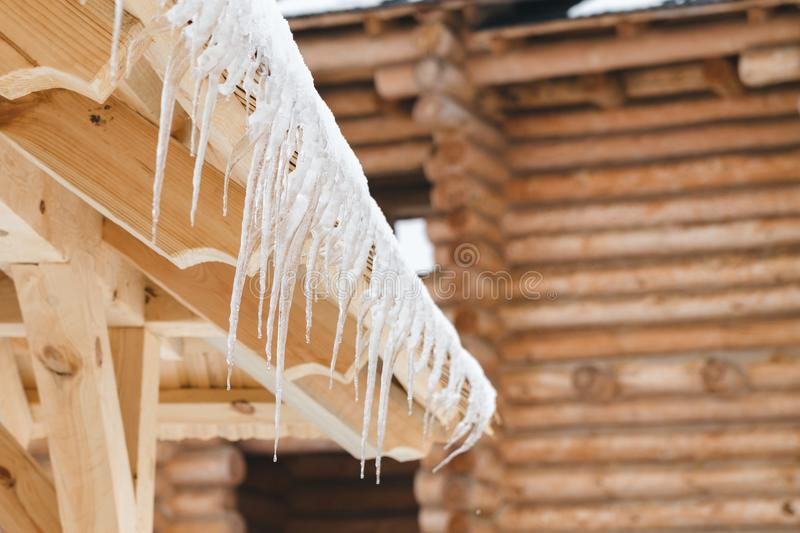 Many icicles melt on the wooden roof with water drops. Spring is comming. Many beautiful icicles melt on the wooden roof at the end of winter and water drops stock photography