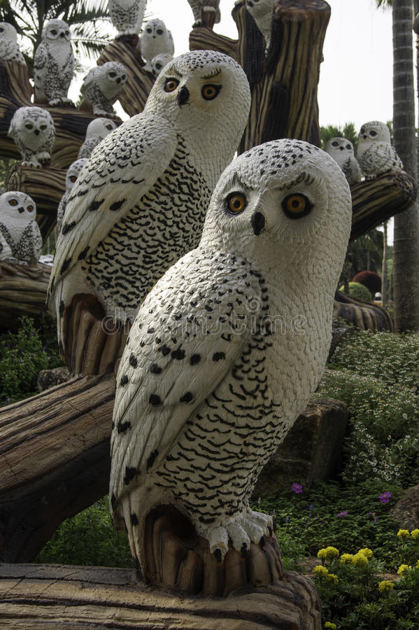 Many big ceramic owls in the garden stock photos