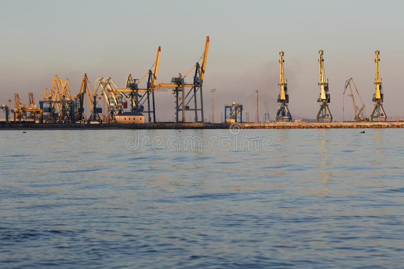 Many big cranes silhouette in the port at golden light of sunset. Mariupol, Ukraine. Many big cranes silhouette in the port at golden light of sunset reflected royalty free stock photos