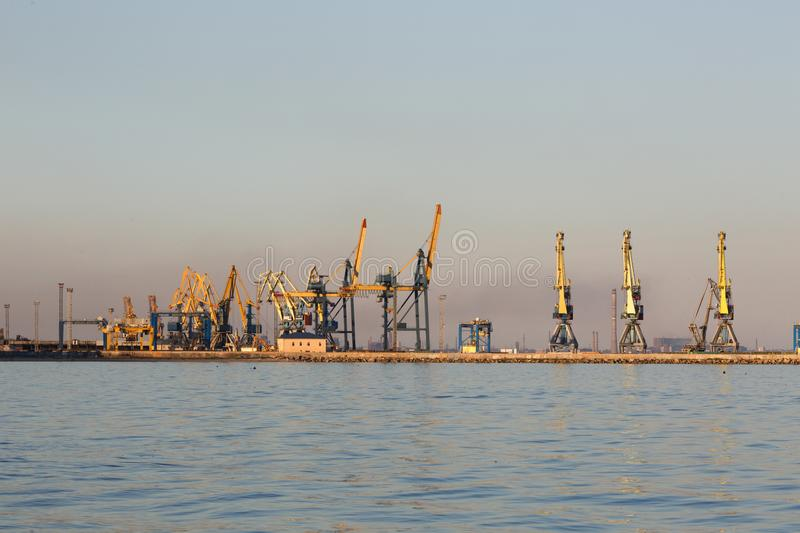 Many big cranes silhouette in the port at golden light of sunset. Mariupol, Ukraine. Many big cranes silhouette in the port at golden light of sunset reflected royalty free stock image