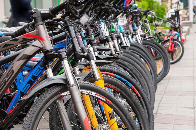 Many bikes of different brands and colors are arranged in orderly rows for sale royalty free stock photo