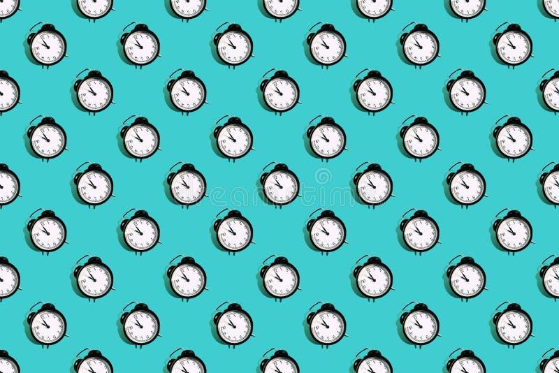 Many black classic style alarm clock isolated on blue background. Many black classic style alarm clock with hard shadow isolated on blue background. Smile time stock image