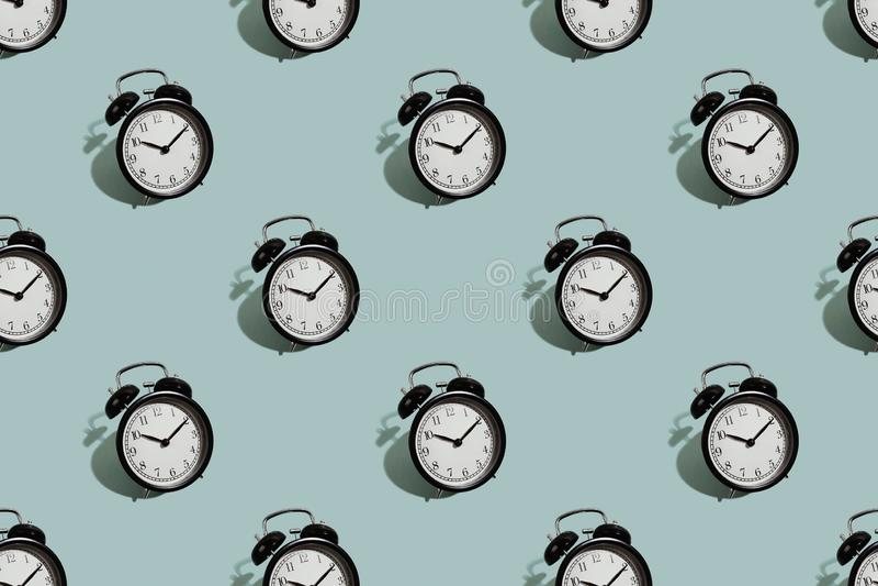 Many black classic style alarm clock isolated on green background. Many black classic style alarm clock with hard shadow isolated on green background. Smile time stock photos